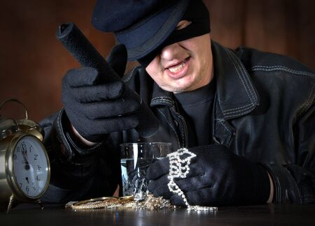 stealer: Burglar with his hands full of jewellery, shining with a torch Stock Photo