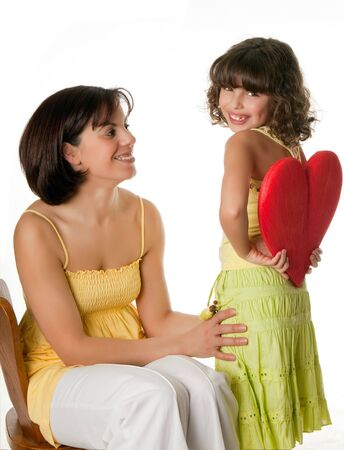 Little girl hiding a big red heart for mothers day photo