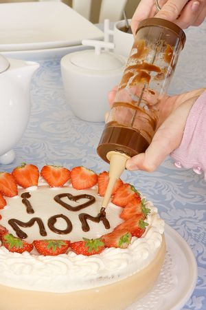 Hands writing Mommy on a mothers day cake photo
