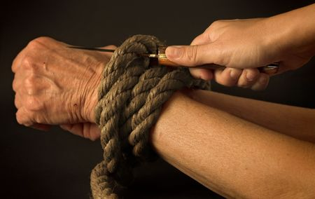 tightened: Hand cutting the rope of a tied person Stock Photo