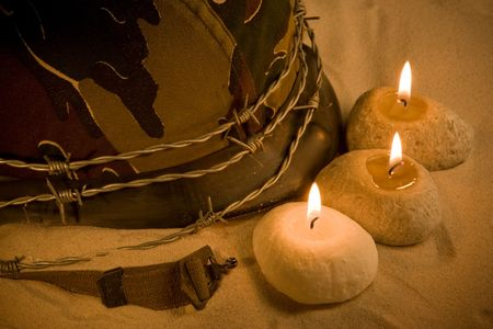 Helmet, barbed wire and candles in the sand photo