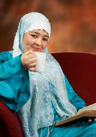 purdah: Young veiled woman sitting on a sofa and reading a book