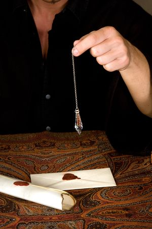Fortune-teller holding a pendulum above vintage letters photo