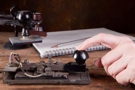 tapping: Mano toccando codice morse su un antico telegrafo macchina
