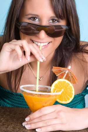 Young woman drinking an orange cocktail with a smile Stock Photo - 4722243