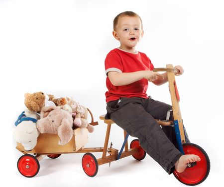transporting: Little boy transporting his teddy bears and dolls in a cart