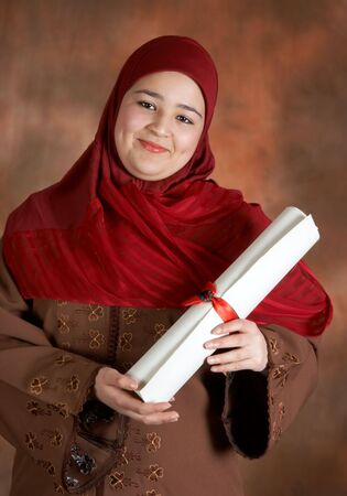 Happy islamic student with diploma, wearing her traditional veil  photo