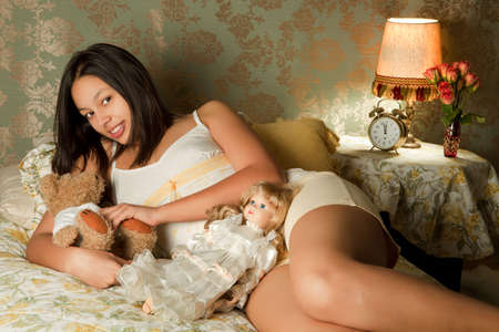 Pretty young lady in her bedroom with teddy bear and doll photo
