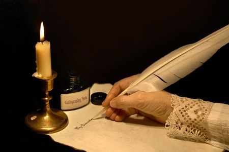 pluma de escribir antigua: Mano escribiendo una carta con una pluma de ganso Foto de archivo