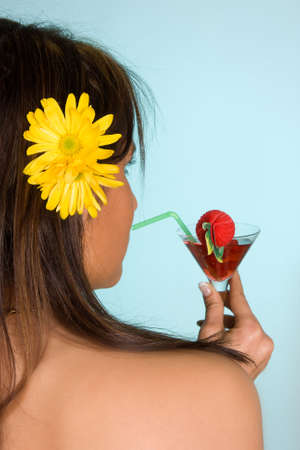 Young woman drinking a red summer cocktail with a straw Stock Photo - 4779738