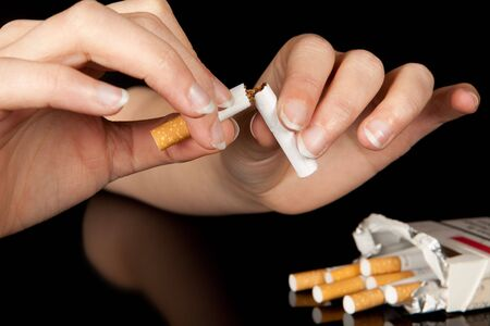 Hand breaking the last cigarette to stop smoking photo