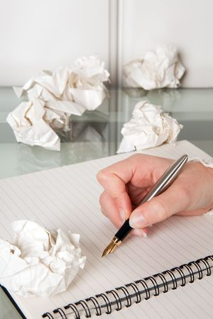 Writing hand surrounded by crumpled balls of paper photo