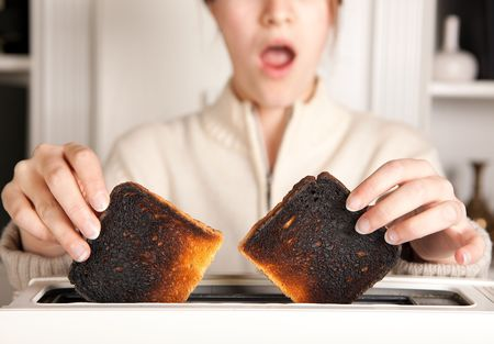burnt toast: Hands of a woman taking burnt toast out of a toaster