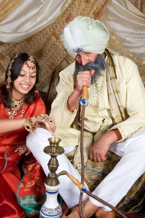 turban: Exotic woman and man demonstrating a water pipe