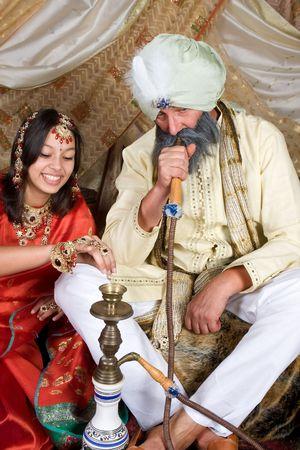 bollywood: Exotische vrouw en man die een waterpijp Stockfoto