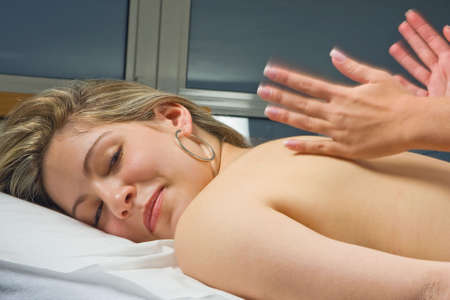 treating: Female hands treating a woman with a back massage Stock Photo
