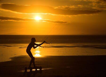 kiter: Silhouette of a kiter against a smashing beach sunset