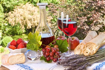 Country-style setting with wine, fruit, bread and cheese Stock Photo - 4826785