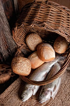Religious still life of loaves of bread, fishing net, basket and two fresh fish photo