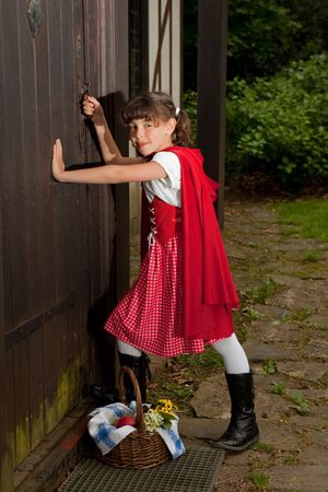 Little red riding hood entering the cottage of her grandmother Stock Photo