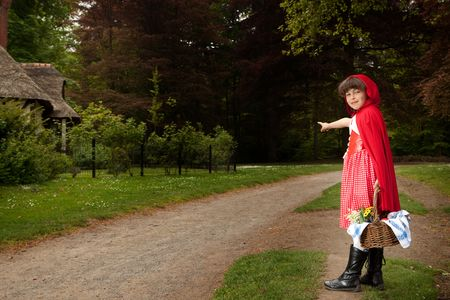 riding wolf: Little red riding hood pointing at her grandmas house in the forest Stock Photo