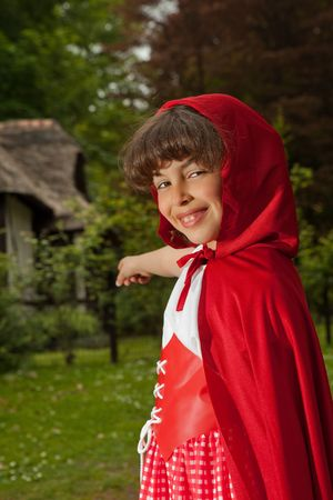 Little red riding hood pointing at her grandma's cottage Stock Photo - 4826121