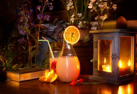 evenings: Pitcher of lemonade on a wooden garden table, a night shot, painted with light
