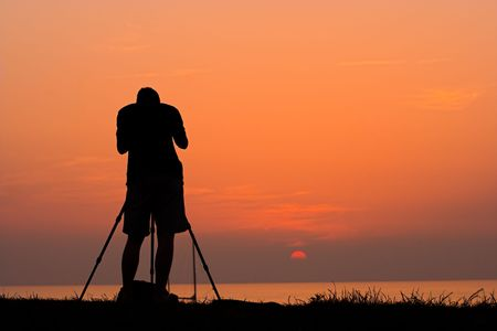 Silhouette of a photographer taking photos of a sunset photo