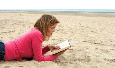 Young blond woman reading a book on the beach photo