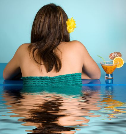 Young woman with cocktail reflected in a swimming pool photo
