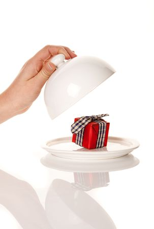 uncovering: Hand uncovering a little red gift on a white tray