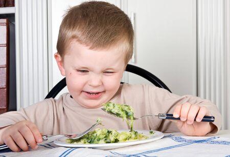dislike: Vier jaar oude jongen zoekt met afschuw op het voedsel op zijn bord Stockfoto