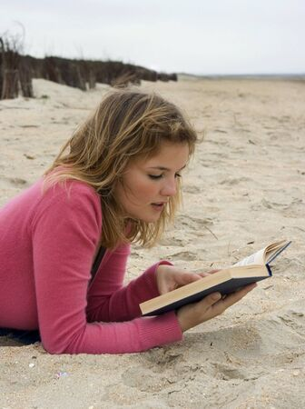 Young student studying or reading on the beach photo