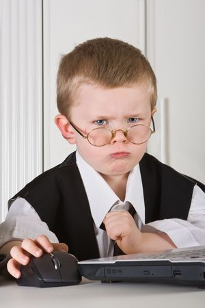 Four year old boy playing angry director in his office photo