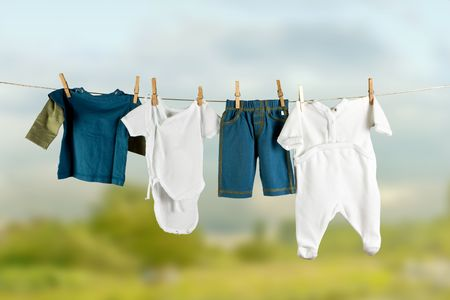 dirty clothes: White and colored baby laundry hanging on a clothesline Stock Photo