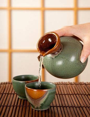 Hand pouring sake in a traditional japanese room