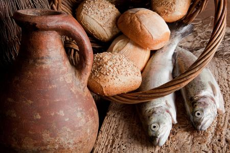 Religious still life of 5 loaves of bread, an antique wine jug and 2 fish photo