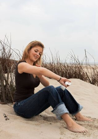 Young blond woman putting on suntan lotion Stock Photo - 4912492