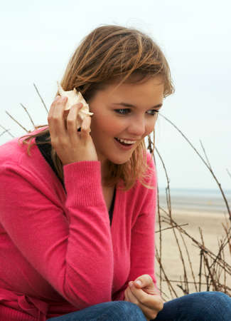 Young blond woman making a phone call with a sea shell photo