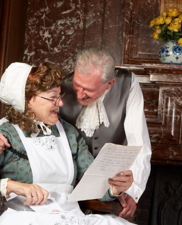 Vintage scene of a Victorian couple reading good news in a letter.Shot in the antique castle