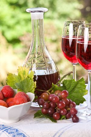 Crystal goblet filled with red wine in a summer setting