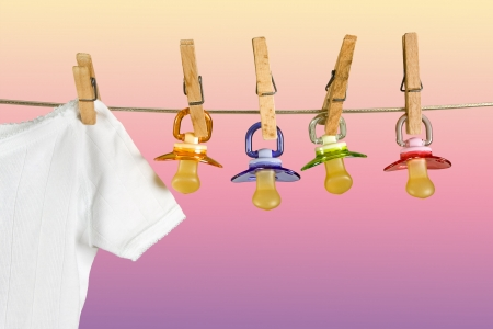 Row of pacifiers hanging next to baby laundry