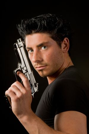 Young man holding a gun against a black background
