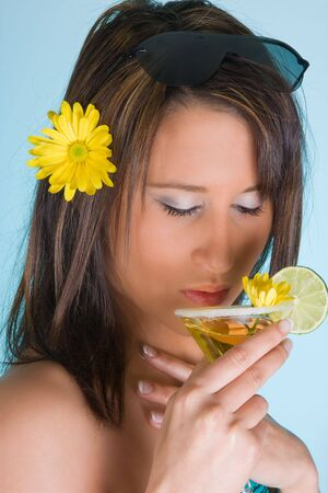 Young woman drinking a yellow summer cocktail photo