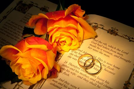Two wedding rings and roses on a bible with Genesis text - the decorations in the book are copied from a 400 years old bible. Stock Photo