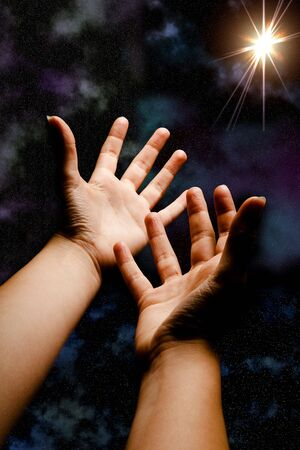 Hands in outer space reaching for a brilliant star Stock Photo - 4944178