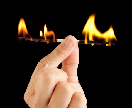 Hand holding a match burning at both ends