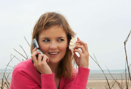 Beautiful young woman talking on the phone through a cell phone and a sea shell photo