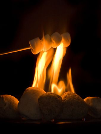toasted: Stick with four marshmallows held above burning fire Stock Photo