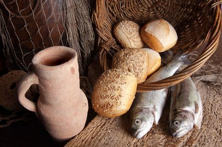 Vintage still life of an old wine jug with bread loaves and fresh fish photo
